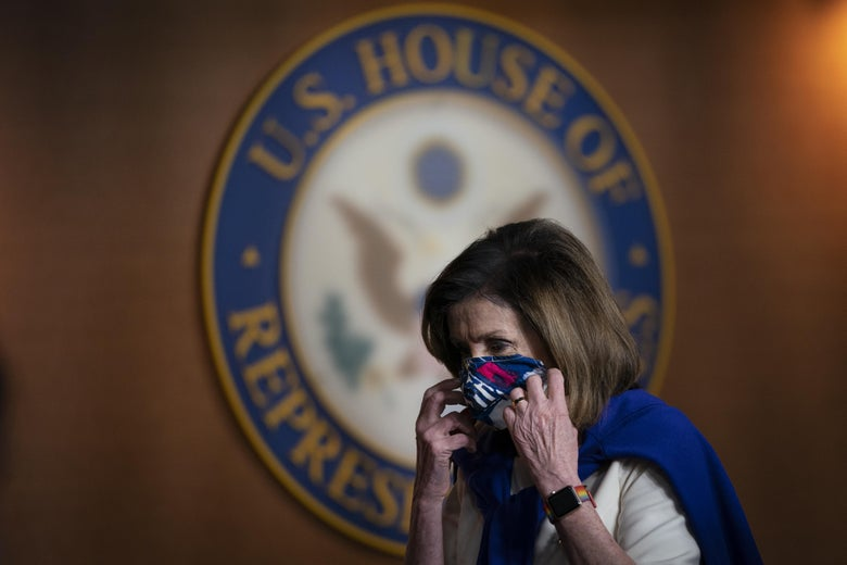 Nancy Pelosi puts on a mask in front of a U.S. House of Representatives sign.