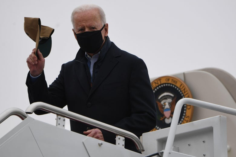 Biden stands at the top of the stairs disembarking from Air Force One, wearing a black mask and holding up a baseball cap