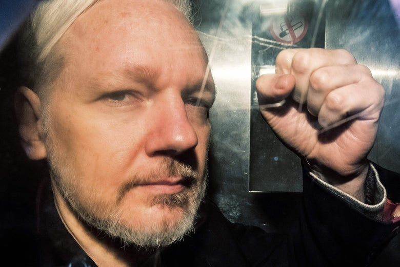 WikiLeaks founder Julian Assange gestures from the window of a prison van.