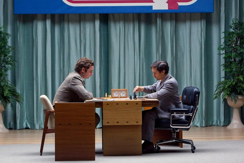 The two men sit at opposite sides of the chess board, a chess clock in the center