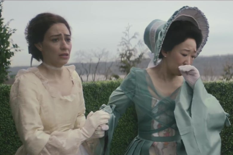 Melissa Villaseñor and Sandra Oh in period outfits, standing in an English garden looking anguished.