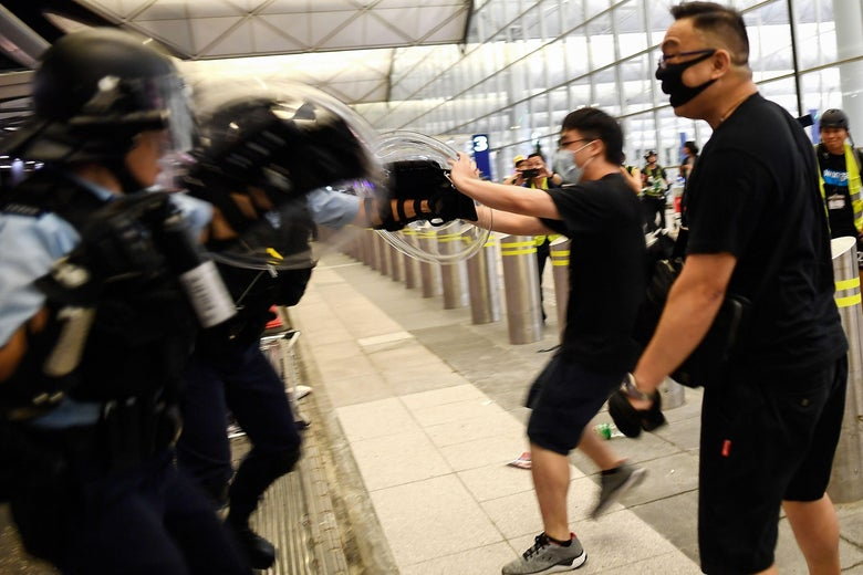 Police scuffle with pro-democracy protesters at the airport.