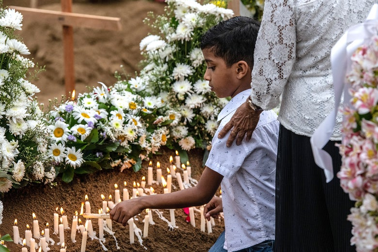 A young boy lights a candle at a grave after a funeral for a person killed in the Easter Sunday attack on St. Sebastian's Church.