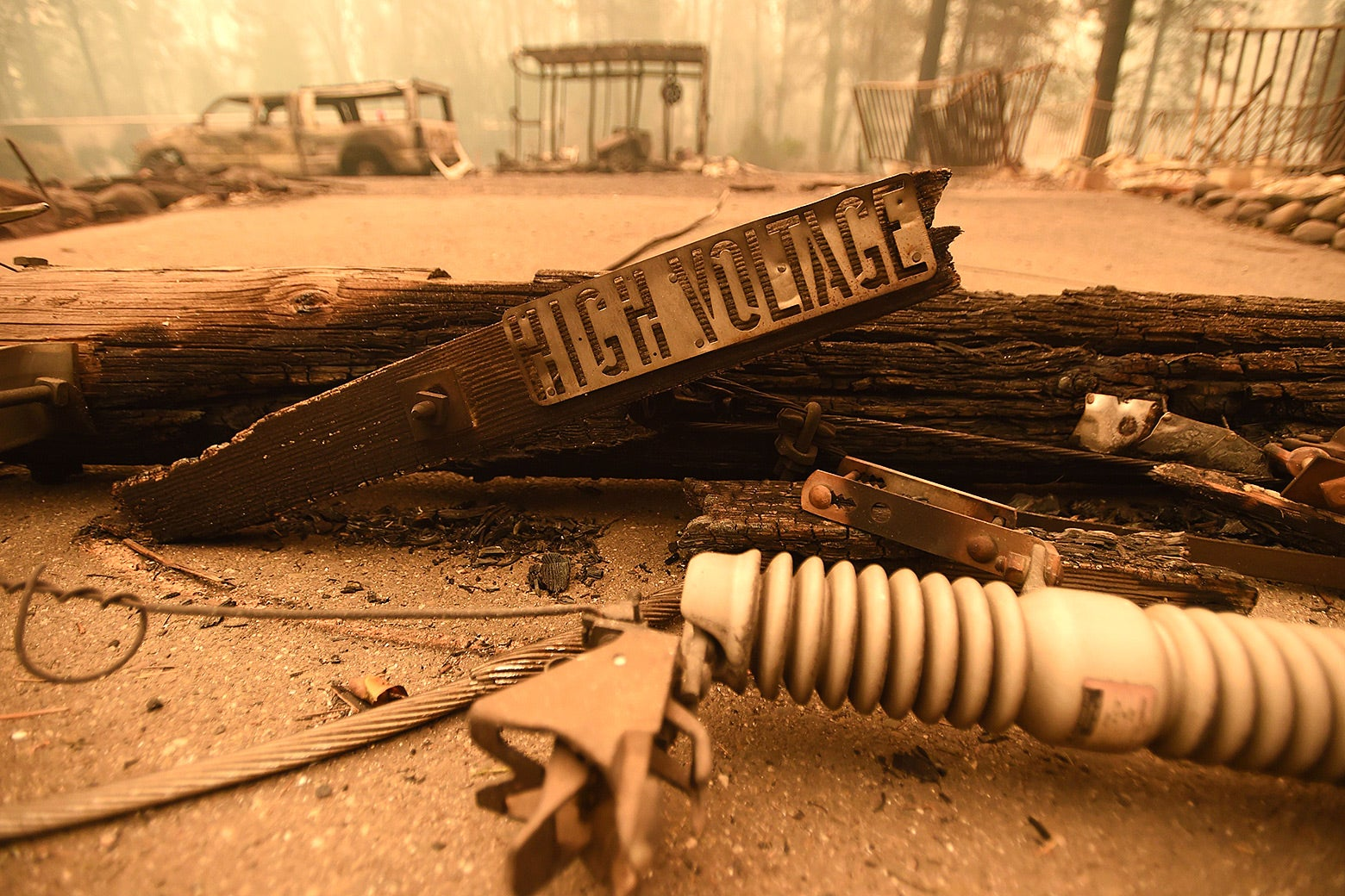 Scorched power lines and a sign reading high voltage.