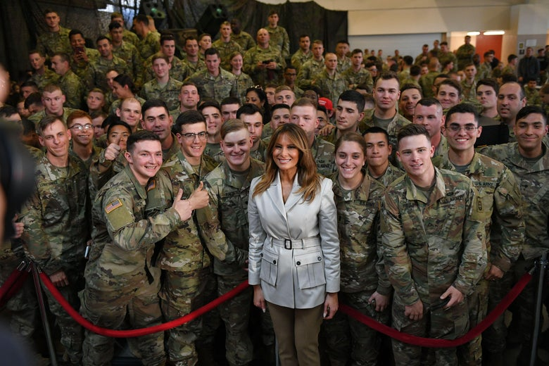 Melania Trump stands in front of a red velvet rope, behind which is a large group of people in camouflage military uniforms. Melania wears a belted taupe jacket with lapels and two cargo pockets, and slim olive green pants.