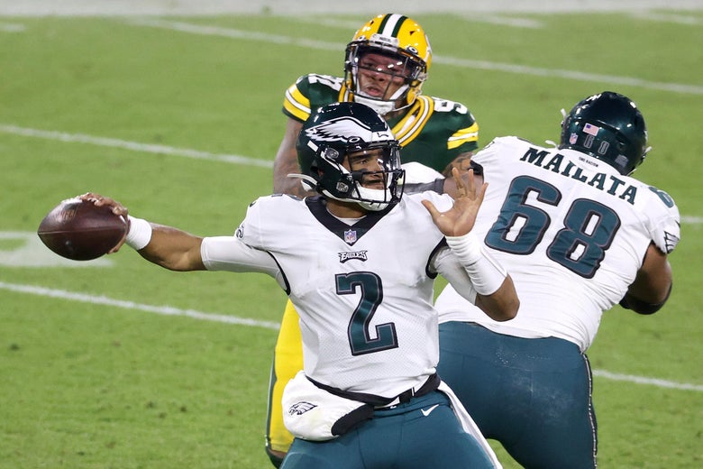 Jalen Hurts passing as two Eagles' linemen block Green Bay Packers pass rushers
