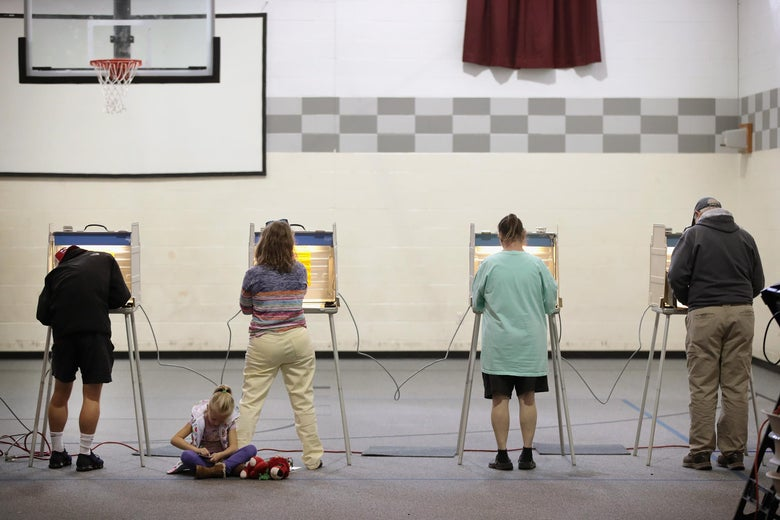 Four people fill out ballots at voting booths in a gymnasium.