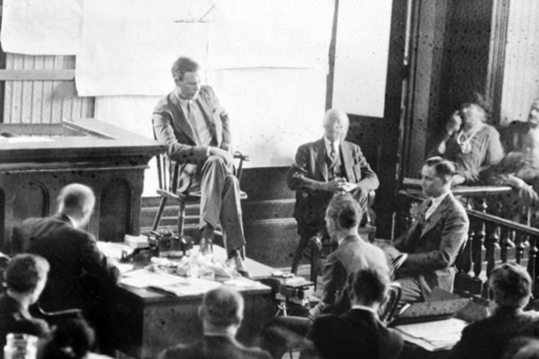 A black-and-white photo shows a man in a suit sitting on a wooden chair on a raised platform at the front of a courtroom.