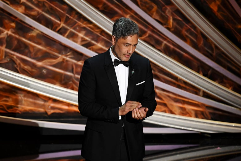 Taika Waititi, in a tux, speaking on a stage.