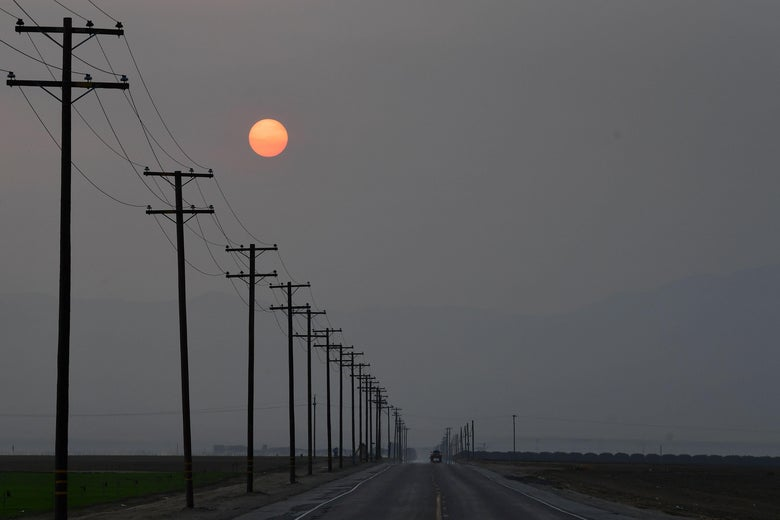 A red sun rises in the smoky sky above an open road