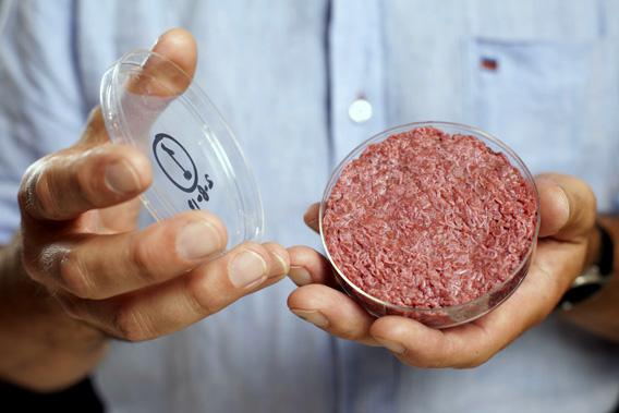 Professor Mark Post holds the world's first lab-grown beef burger during a launch event in west London August 5, 2013.