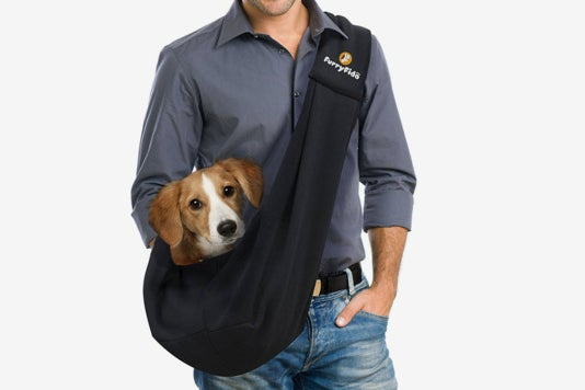 Man carrying a dog in the FurryFido Pet Sling.
