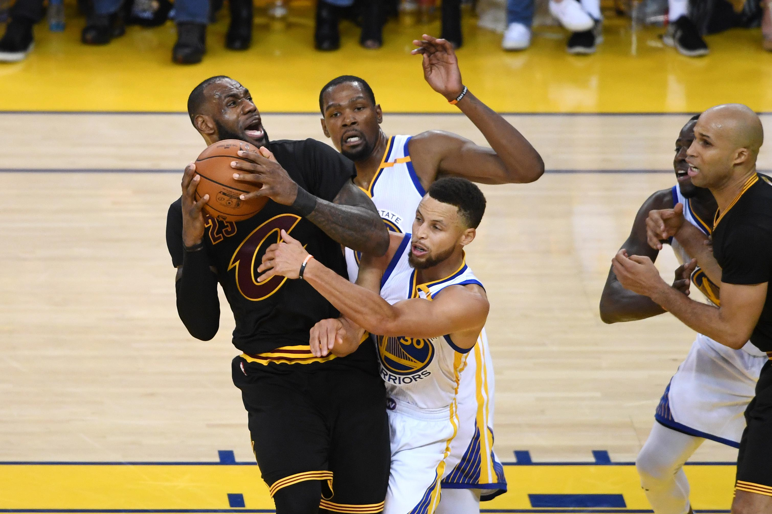 OAKLAND, CA - JUNE 12: LeBron James #23 of the Cleveland Cavaliers is defended by Kevin Durant #35 and Stephen Curry #30 of the Golden State Warriors during the second half in Game 5 of the 2017 NBA Finals at ORACLE Arena on June 12, 2017 in Oakland, California. NOTE TO USER: User expressly acknowledges and agrees that, by downloading and or using this photograph, User is consenting to the terms and conditions of the Getty Images License Agreement.  (Photo by Thearon W. Henderson/Getty Images)