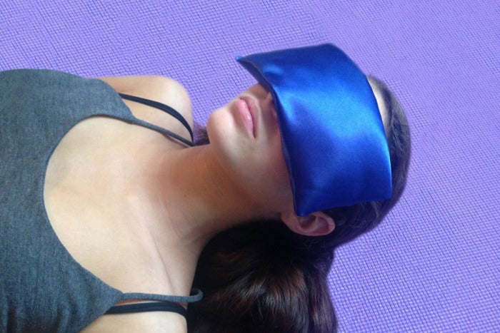 Woman wearing the AyaZen Lavender Eye Pillow over her eyes.