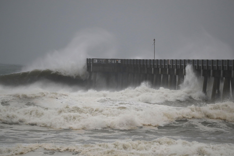 Storm waves crash against a pier.