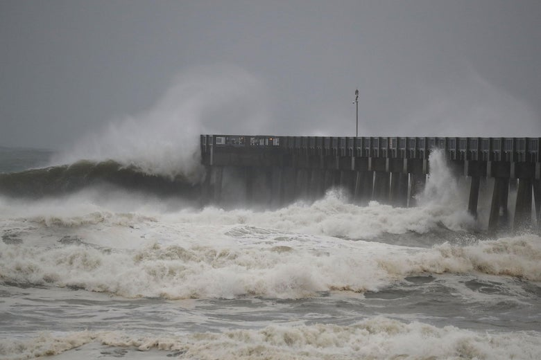 Storm waves crash against a pier.