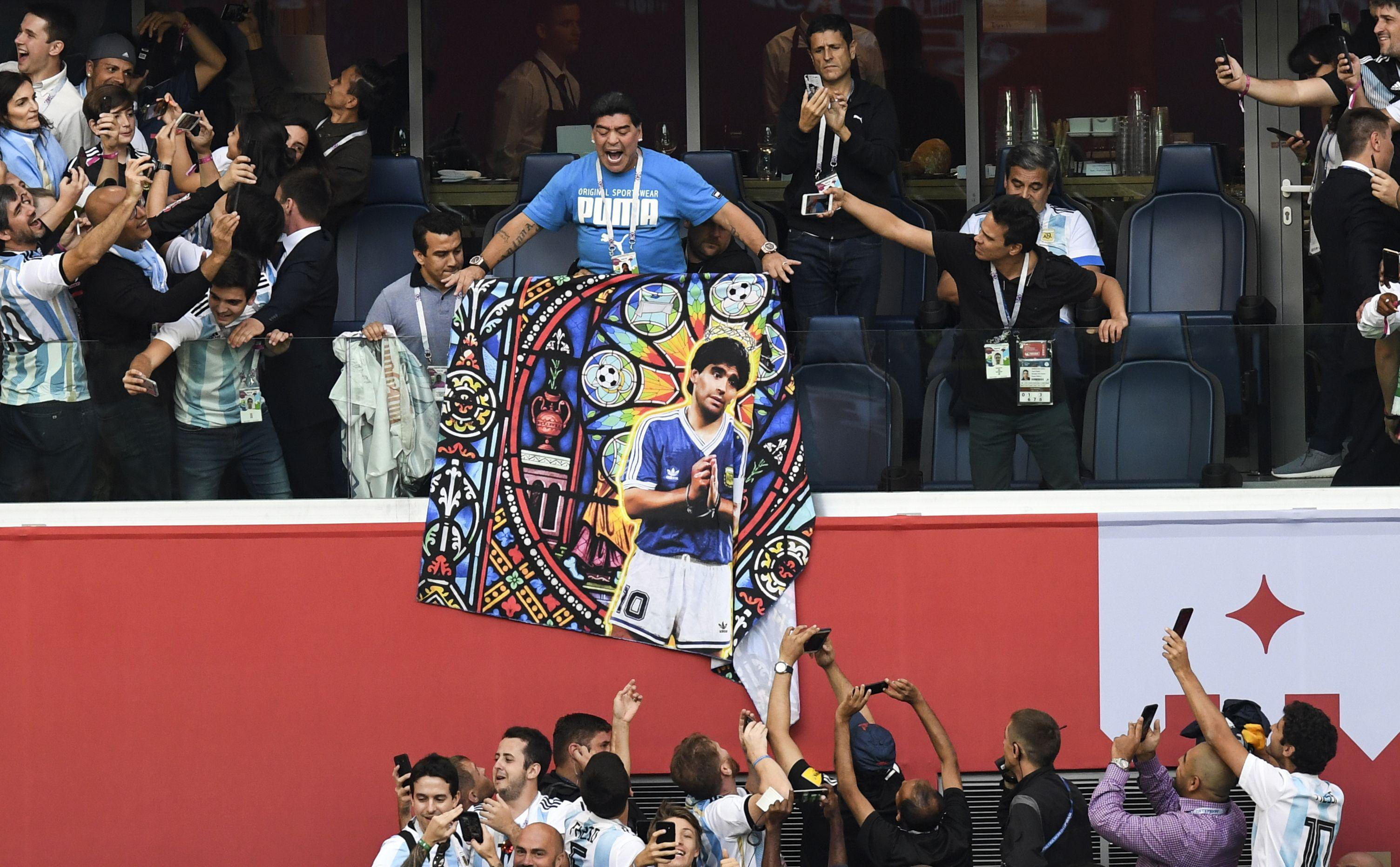 Retired Argentina forward Diego Maradona carries a poster bearing his portrait ahead of the Russia 2018 World Cup Group D football match between Nigeria and Argentina at the Saint Petersburg Stadium in Saint Petersburg on June 26, 2018. (Photo by Paul ELLIS / AFP) / RESTRICTED TO EDITORIAL USE - NO MOBILE PUSH ALERTS/DOWNLOADS        (Photo credit should read PAUL ELLIS/AFP/Getty Images)