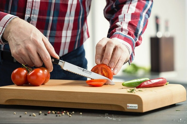 Man slicing a tomato with a knife.