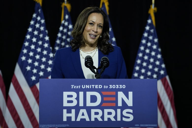 Harris speaks at a podium bearing the Biden-Harris campaign logo, with American flags in the background