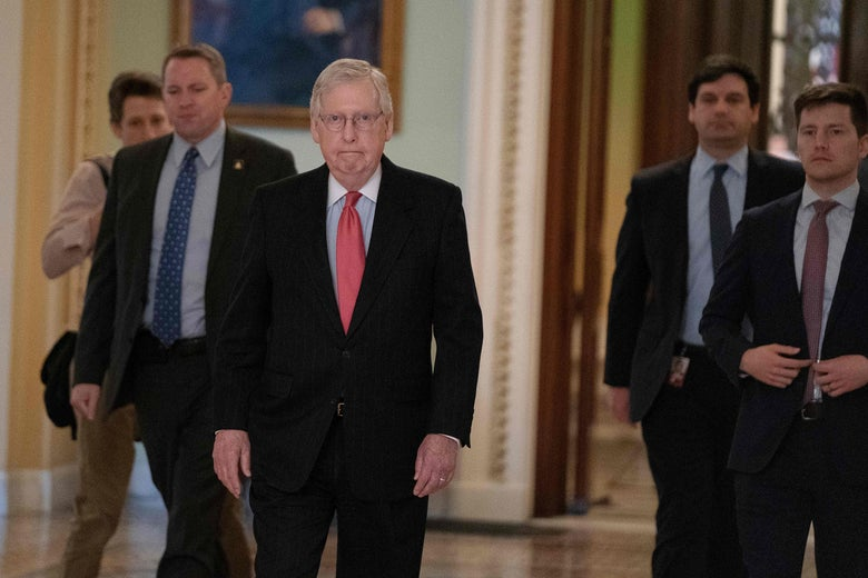 Mitch McConnell walking through the halls of Congress with other men around him