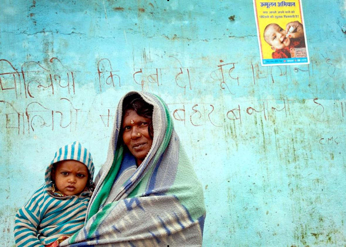 A mother and child pose in front of a polio eradication slogan a