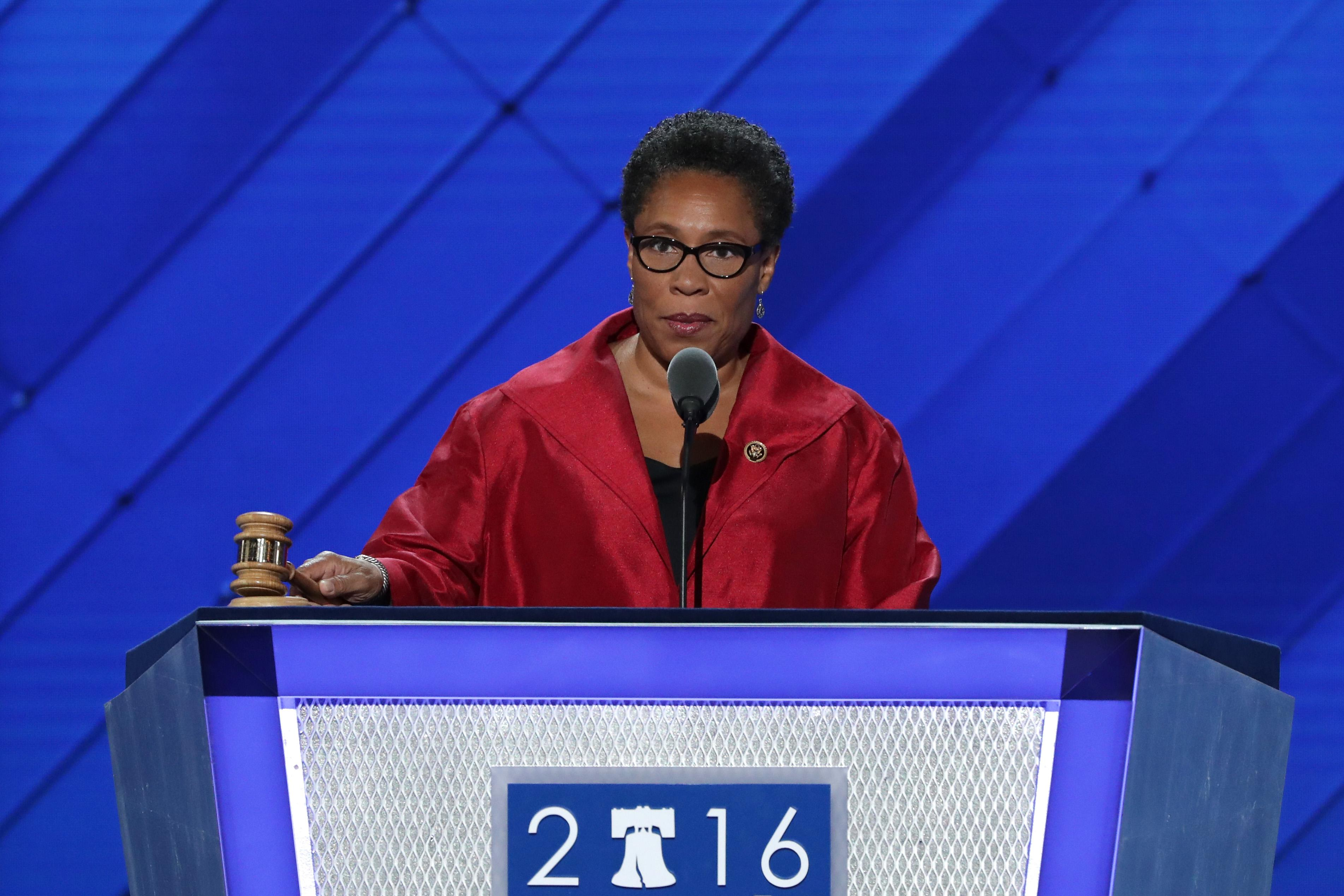 "Marcia Fudge, dressed in red, holds a gavel at a podium with ""2016""—the ""0"" replaced by a drawing of the Liberty Bell—on the front. The backdrop and the podium are both blue."