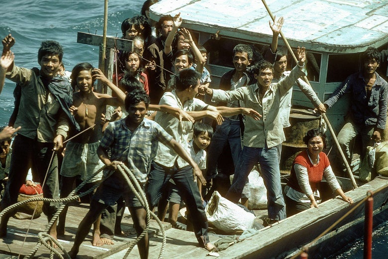 A group of Vietnamese boat people on board of their nautical vessel visibly happy to be rescued.