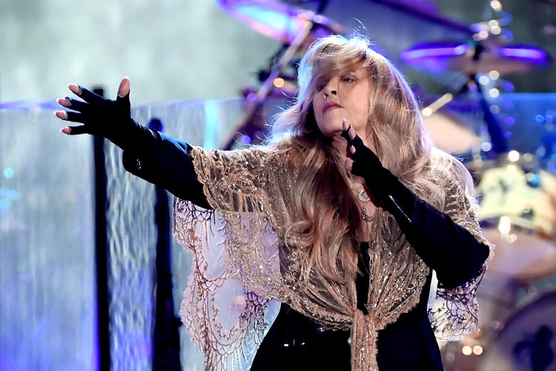 Stevie Nicks, wearing a glittering shawl and fingerless gloves, gestures dramatically onstage.