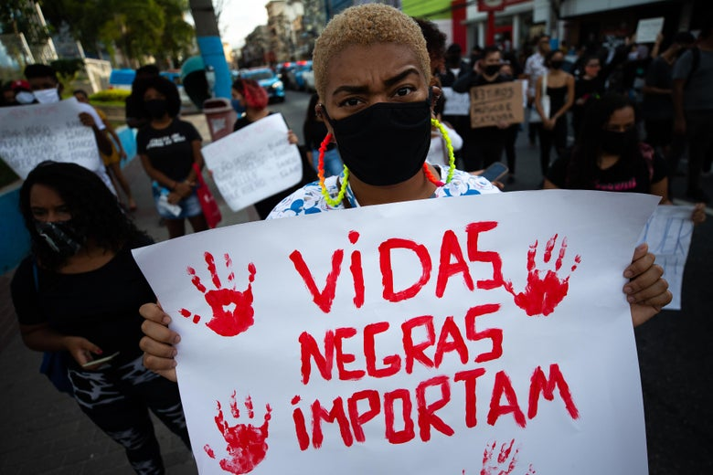 "A woman in a mask holds a red-painted sign reading ""Black Lives Matter"" in Portuguese at a rally."