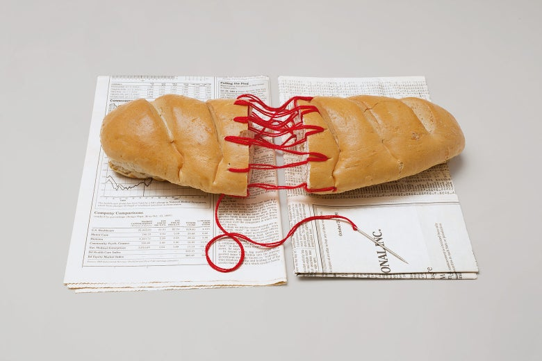 A sculpture of a loaf of bread stitched together with red string.