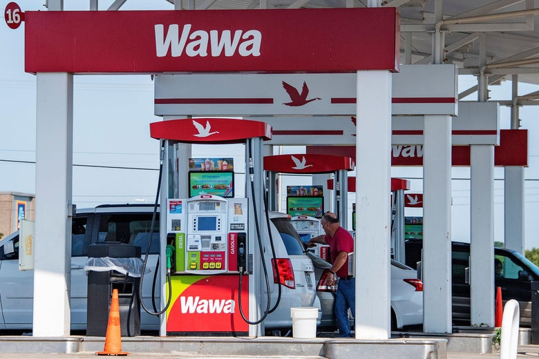 A man fills up his car with gas at a Wawa gas station.