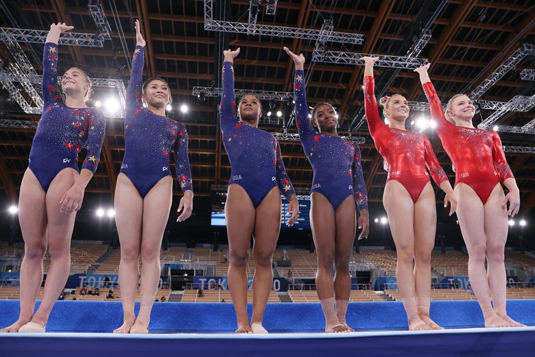 The six American gymnasts stand in front of the floor apparatus and wave. Grace McCallum, Sunisa Lee, Jordan Chiles, and Simone Biles wear blue leotards. MyKayla Skinner and Jade Carey wear red as individual nonteam competitors.
