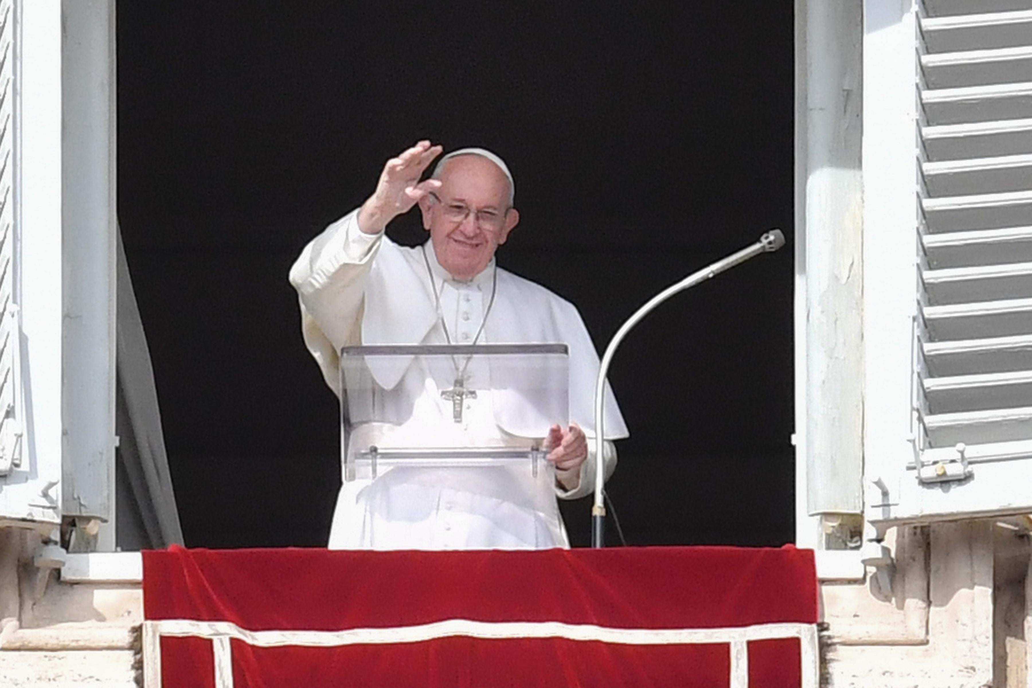 Pope Francis waves from his window of the Apostolic Palace overlooking St. Peter's square.