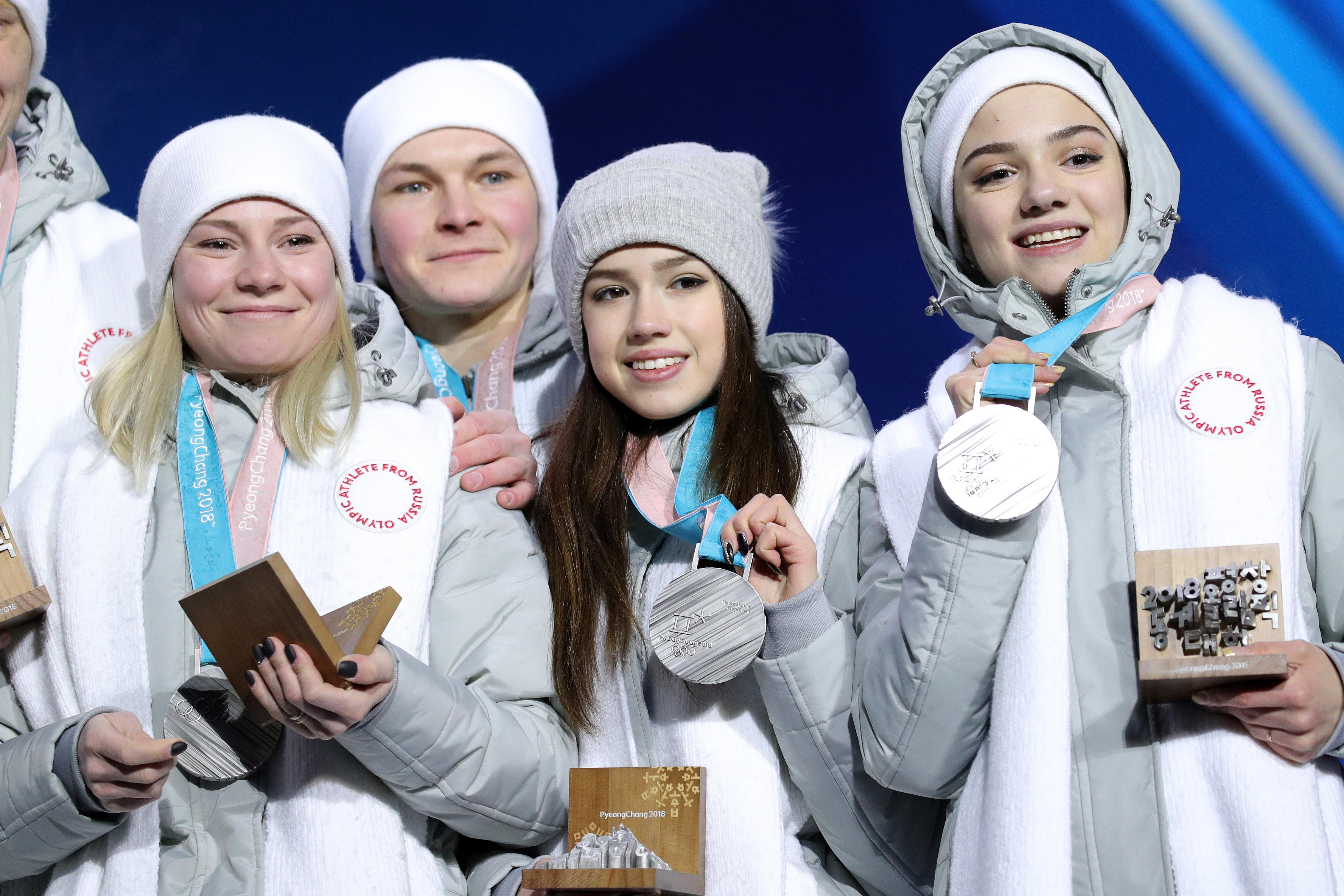 Four Olympic Athletes from Russia display the silver medals they won in the team figure skating event at the Pyeongchang Olympics.