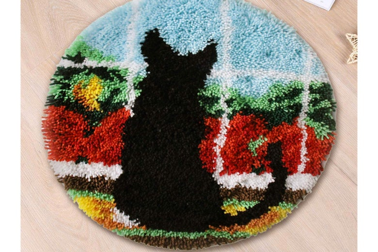 A round rug with a black cat looking out the window.