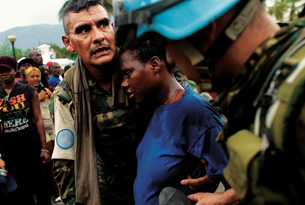 United Nations peacekeepers from Uruguay tend to pregnant Haitian woman who lost consciousness in a massive crowd during a rice distribution for earthquake-displaced Haitians on Jan. 25, 2010, in Port-au-Prince, Haiti.