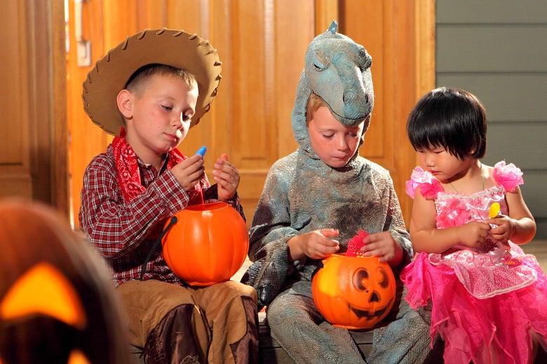 Three children going through Halloween candy.