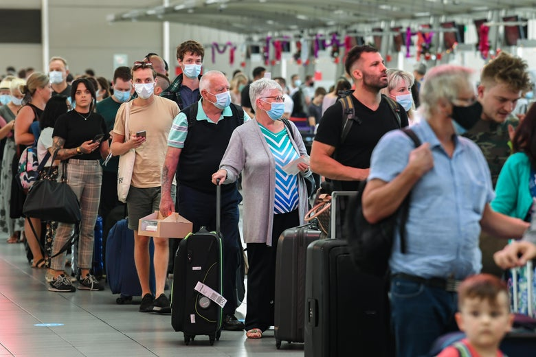 People, some wearing masks, stand in line with luggage in an airport.