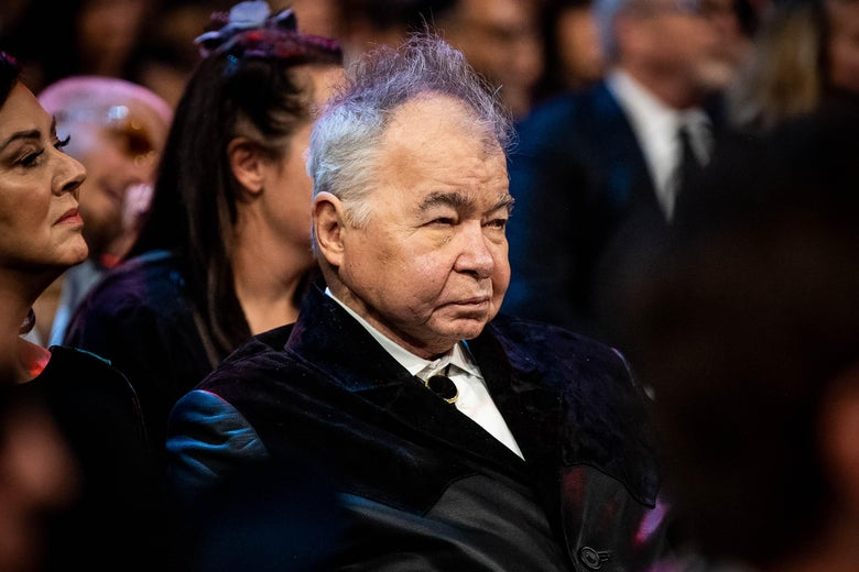 John Prine, in a velvet jacket and bolo tie, sitting in the audience at the Grammys.