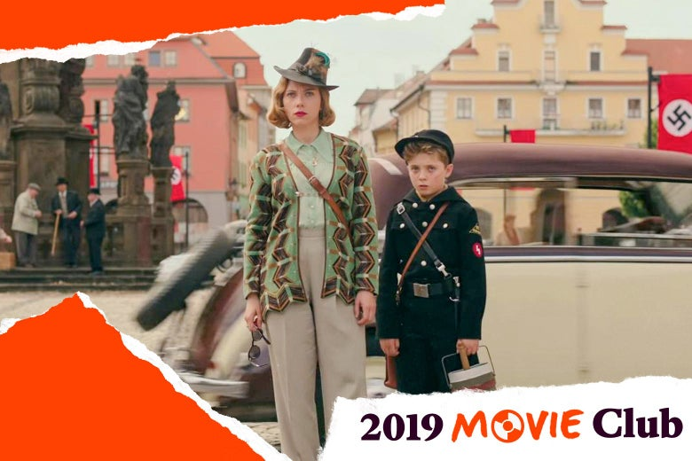 "Scarlett Johansson stands next to the Jojo actor in a town square in a still from Jojo Rabbit. Text in the corner says, ""2019 Movie Club."""
