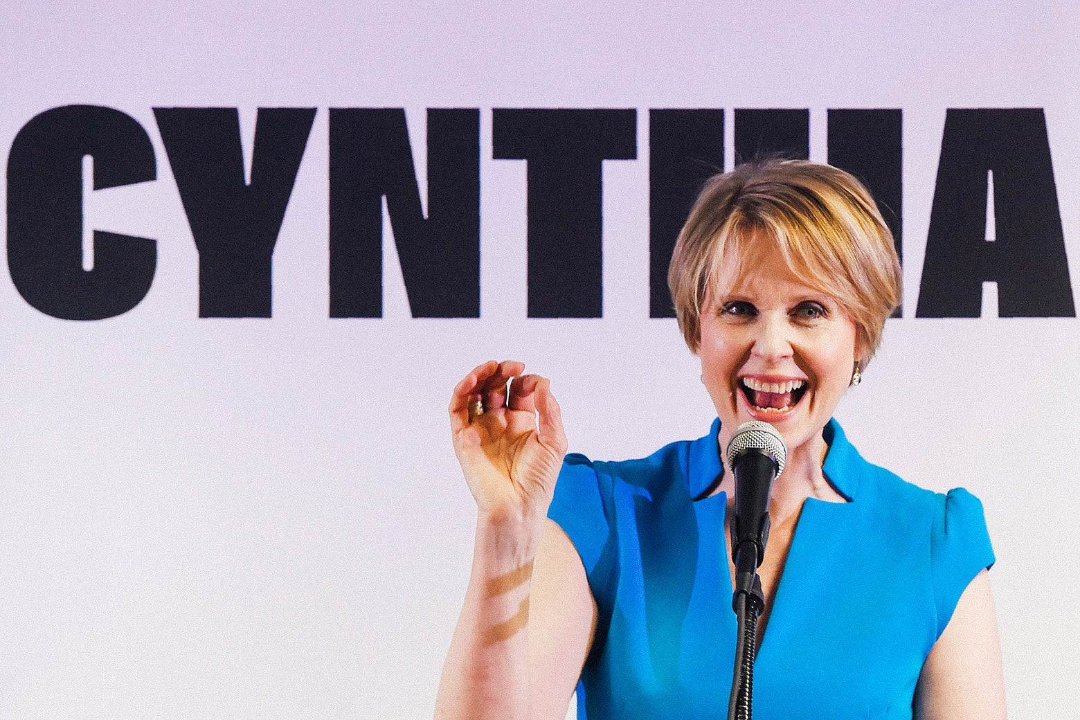 Cynthia Nixon standing in front of a campaign sign that says Cynthia.