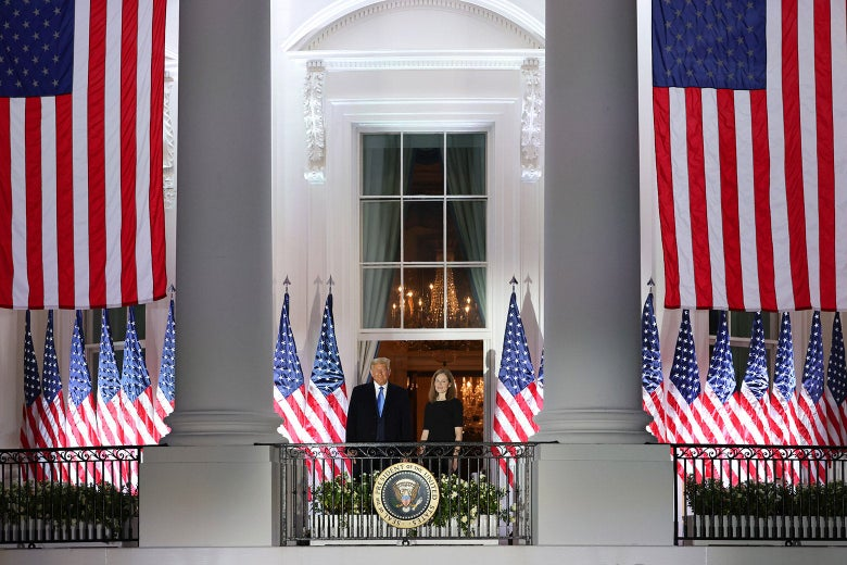 Trump and Barrett stand on a balcony overlooking the South Lawn, with American flags all around them