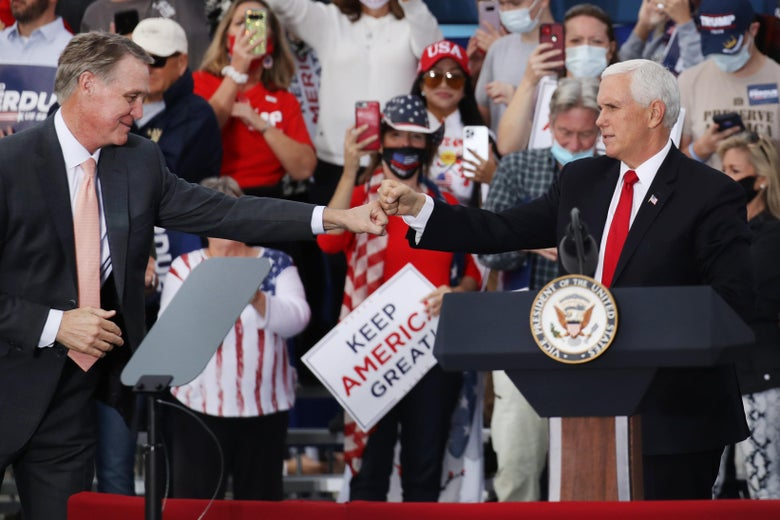 Pence and Perdue fist-bumping on stage