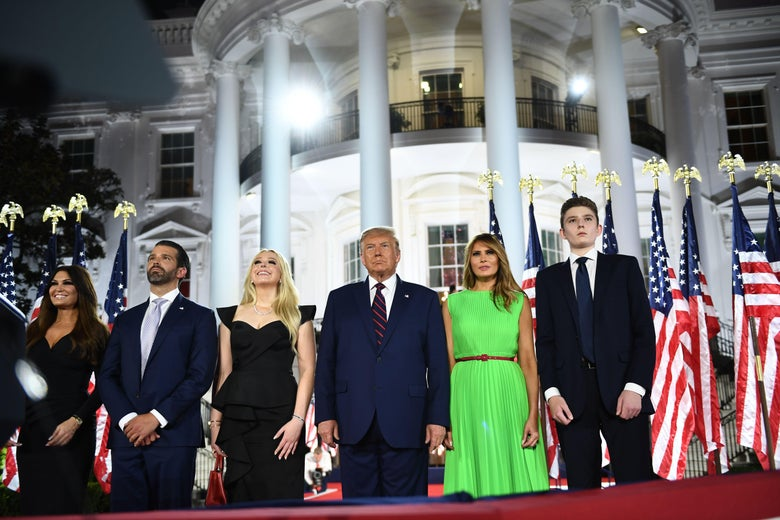 Kimberly Guilfoyle, Donald Trump Jr., Tiffany Trump, Donald Trump, Melania Trump, and Barron Trump stand shoulder to shoulder in front of a row of U.S. flags and the White House. Everyone is wearing dark blue and black, except Melania, who is wearing a sleeveless lime green pleated dress with a thin red belt.