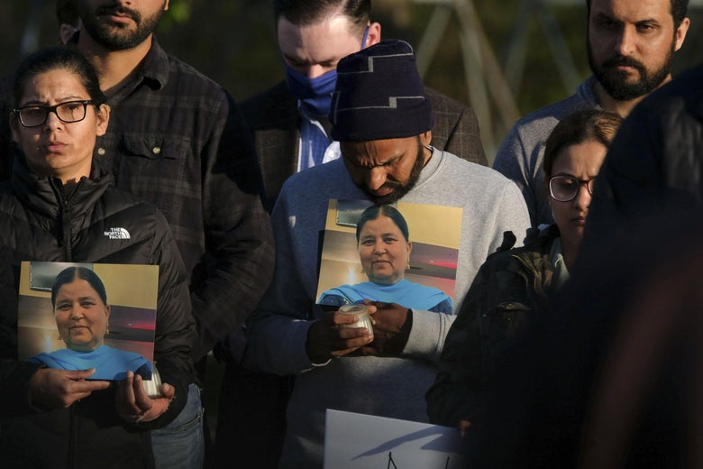 Family members hold a photo of their loved one during a candlelight vigil in Krannert Park in Indianapolis, Indiana, April 17, 2021, to remember the victims of a mass shooting at a local FedEx facility.