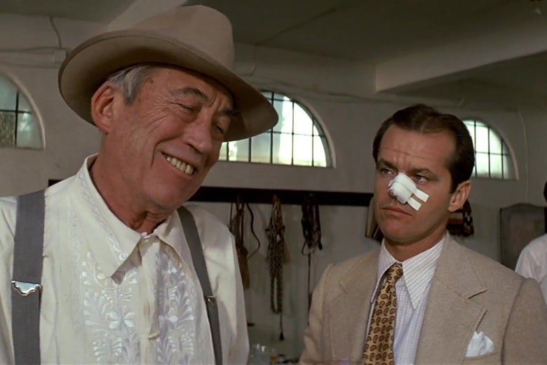 John Huston, as Noah Cross in Chinatown, wearing a shirt and suspenders and smiling amiably. Jack Nicholson, as Jake Gittes, wearing cheaper clothes and a giant bandage on his nose, glaring at Cross.