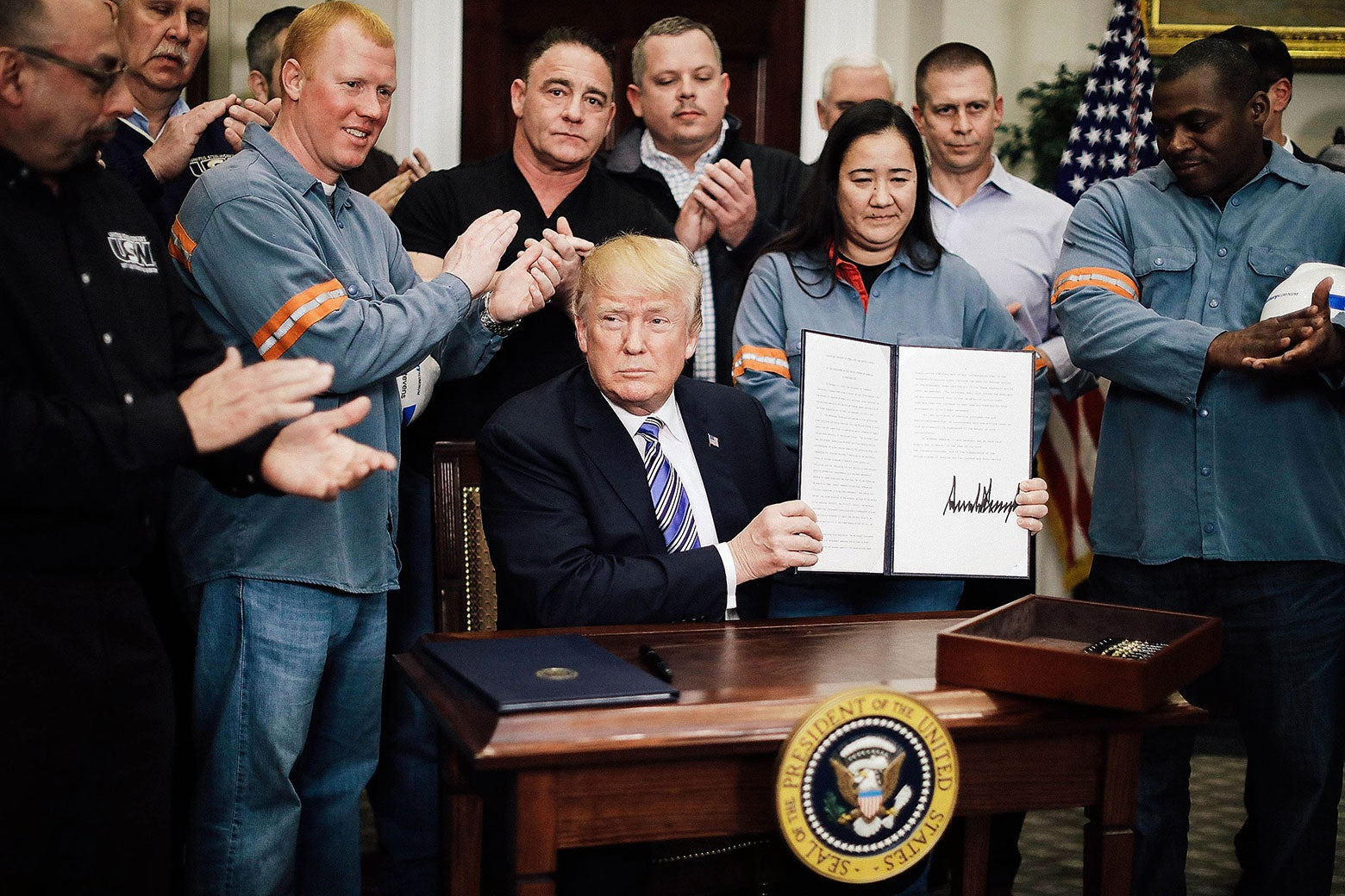 Surrounded by applauding steel and aluminum workers, President Donald Trump holds up the proclamation he signed.