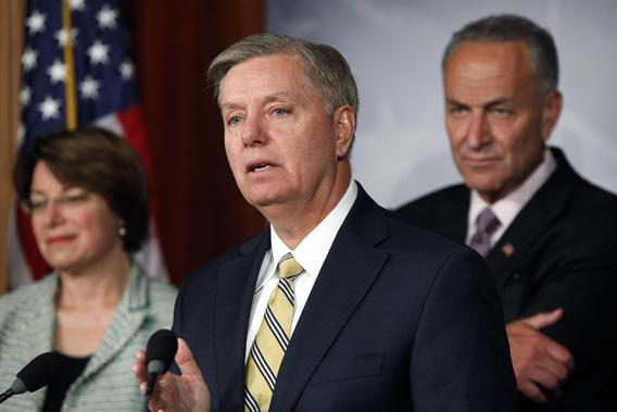 U.S. Senator Lindsey Graham (R-SC) and Senator Chuck Schumer (D-NY) (R) speak during a push for new bipartisan media shield legislation during a news conference at the U.S. Capitol in Washington.
