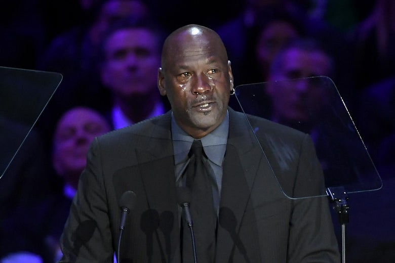 Michael Jordan stands in front of microphones, tears streaming down his face.