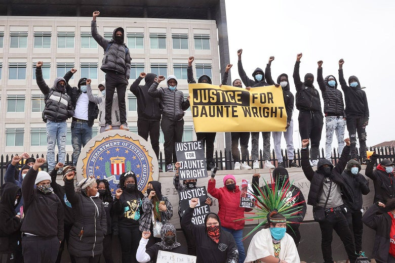"""Protestors hold up fists and """"Justice for Duante Wright"""" signs to raise awareness of the shooting death of Daunte Wright."""